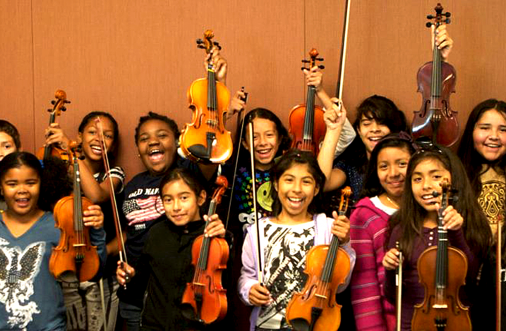 Young violin players showing their violins