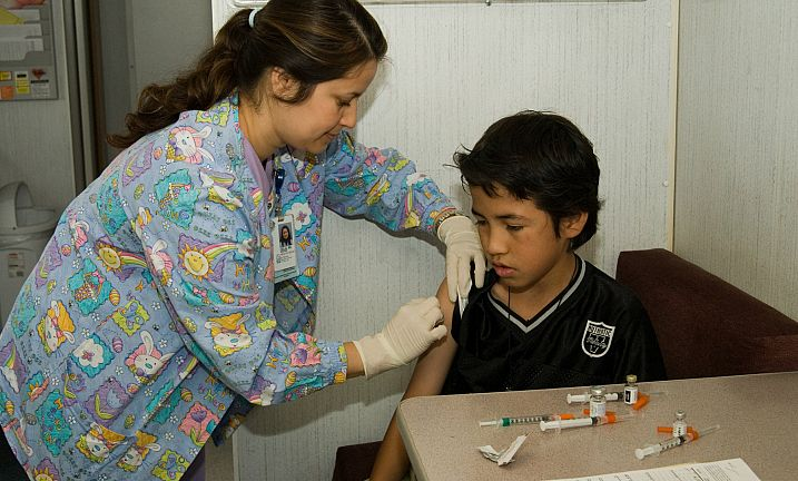 Nurse giving immunization Shot to Child